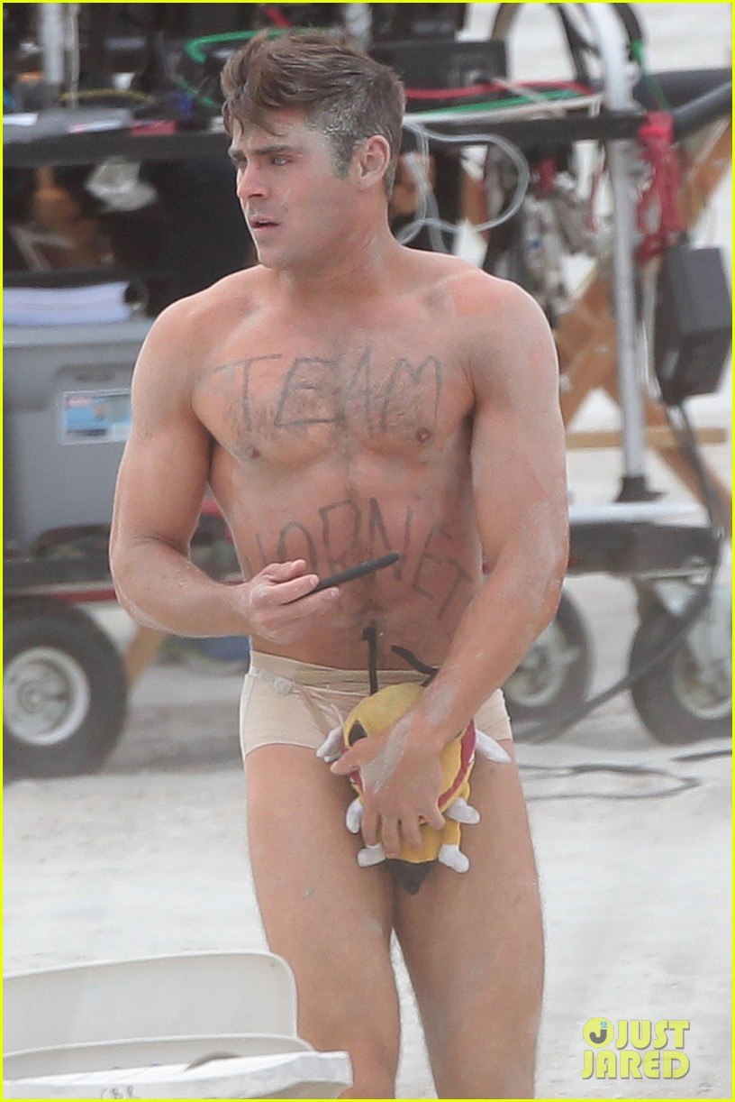 Zac Efron wears just a pair of nude underwear and a stuffed toy to protect his modesty as he films a beach scene for 'Dirty Grandpa'