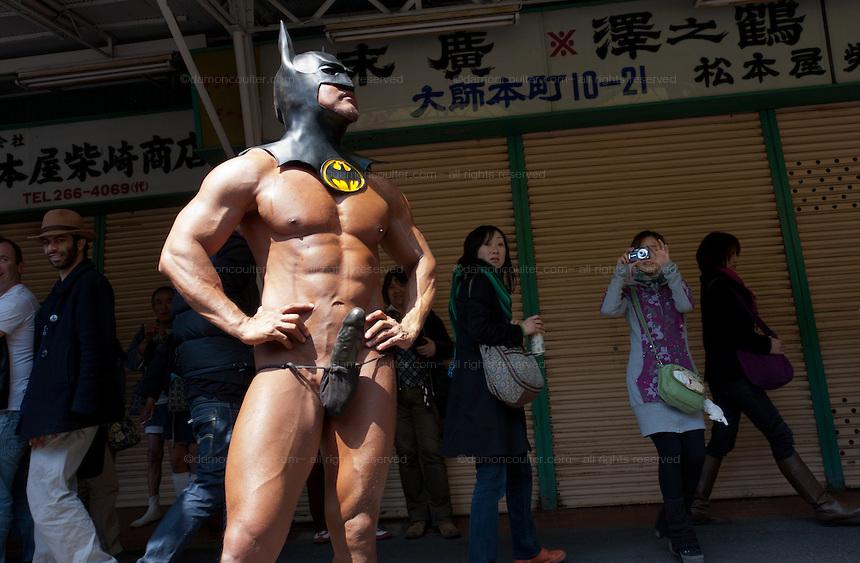A foreign man naked apart from a Batman mask and loincloth with attached phallus poses during the Kanamara matsuri or festival of the iron phallus in Kawasaki Daishi near Tokyo, Japan. Sunday April 1st 2012